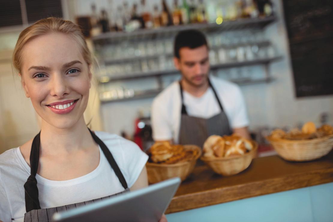 Gastronomie-Gründer hinter und vor einer Theke